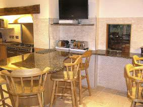 Luxurious kitchen with granite tops, marble tiles and oak furniture